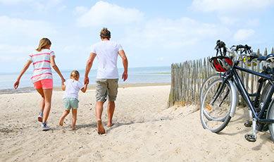 Famille sur la plage avec vélos