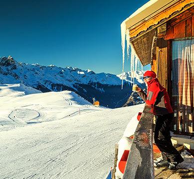 Femme qui boit un café au ski