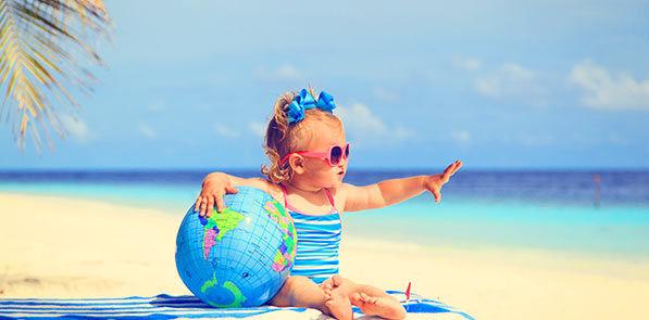 Bébé fille avec globe sur la plage